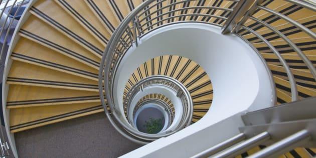 Multi-floor geometric spiral staircase looking downward