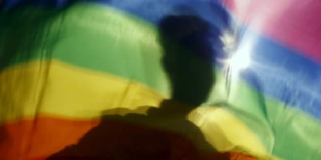 A gay man is silhoutted on a gay rainbow flag during a demonstration for gay rights in Hanoi, Vietnam, November 24, 2015. While transgender, gay and lesbian people are persecuted and even jailed in many Asian countries, Vietnam has quietly become a trailblazer, with laws to decriminalize gay marriage and co-habitation and recognize sex changes on identity documents. Picture taken November 24, 2015. REUTERS/Kham