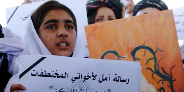 An Iraqi Yazidi woman holds a placards during a protest outside the United Nations (UN) office in the Iraqi city of Arbil, the capital of the autonomous Kurdish region, on August 2, 2015 in support of women from their community who were kidnapped last year in the Sinjar region by the Islamic State (IS) group jihadists. In 2014, the jihadists massacred Yazidis, forced tens of thousands of them to flee, captured thousands of girls and women as spoils of war and used them as sex slaves. AFP PHOTO / SAFIN HAMED        (Photo credit should read SAFIN HAMED/AFP/Getty Images)