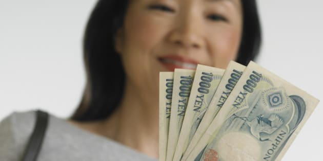 Low angle view of Asian woman holding Japanese money
