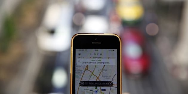 A phone running the Uber application is held above the traffic in central Bangkok December 10, 2014. Thailand has ordered U.S. online taxi booking company Uber to cease operations, on the same day taxi apps were banned in the Indian capital New Delhi where an Uber driver is under arrest for suspected rape.  REUTERS/Damir Sagolj (THAILAND - Tags: SOCIETY SCIENCE TECHNOLOGY CRIME LAW TRANSPORT)