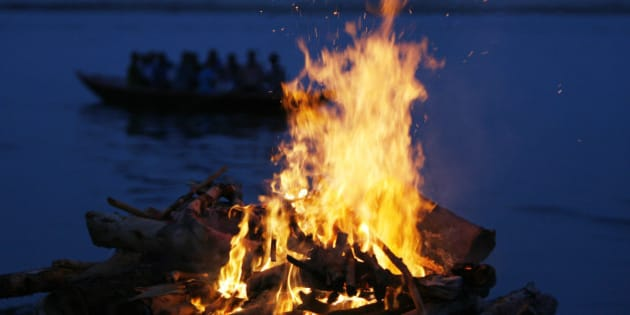 """A tourist boat goes past the burning flames of a pyre at a cremation ground on the banks of river Ganges in Varanasi June 12, 2007. Hindus believe that dying in Varanasi and having their remains scattered in the Ganges allows their soul to escape a cycle of death and rebirth, attaining """"moksha"""" or salvation.   REUTERS/Arko Datta (INDIA)"""