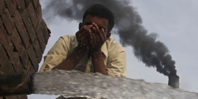 A labourer drinks water as smokes rise from a chimney of a brick factory at Togga village on the outskirts of the northern Indian city of Chandigarh December 6, 2009. India set a goal on Thursday for slowing the growth of its greenhouse gas emissions, the last major economy to offer a climate target four days before the start of U.N. talks on combating global warming. REUTERS/Ajay Verma (INDIA ENVIRONMENT SOCIETY)   FOR BEST QUALITY IMAGE: ALSO SEE GF2E63C14JP01