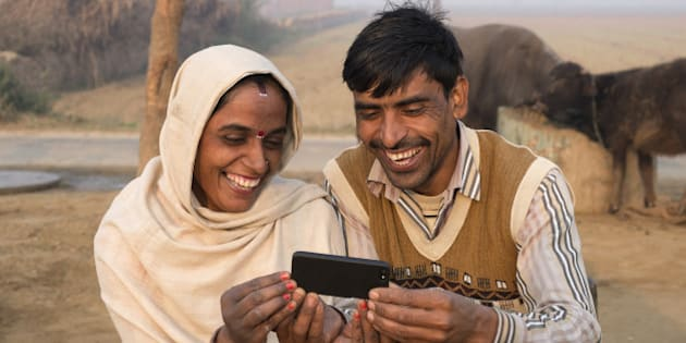 India, Uttar Pradesh, Agra, husband and wife looking at smart phone in rural setting.