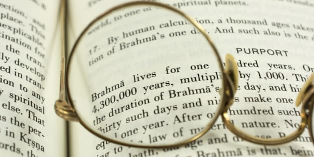 The Hindu Bhagavad Gita book with an old gold pair of glasses.