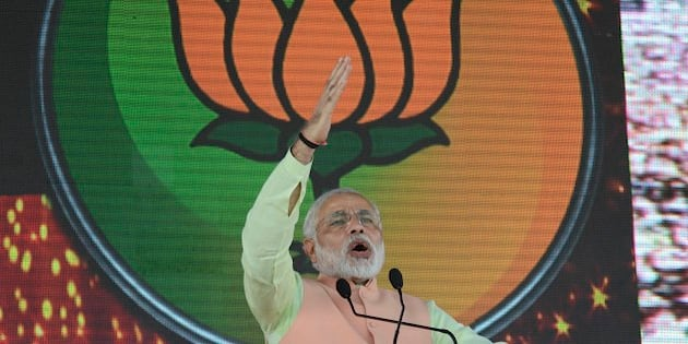 Party symbol Lotus is projected behind as India's main opposition Bharatiya Janata Party (BJP)'s prime ministerial candidate Narendra Modi, addresses a rally in Patna, India, Sunday, Oct.27, 2013. A series of small bomb blasts killed some people and injured dozens Sunday just hours before the campaign rally by Modi. (AP Photo/Aftab Alam Siddiqui)