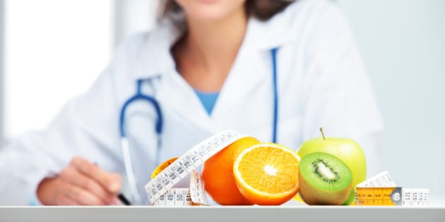Nutritionist female Doctor in her office. Focus on fruit