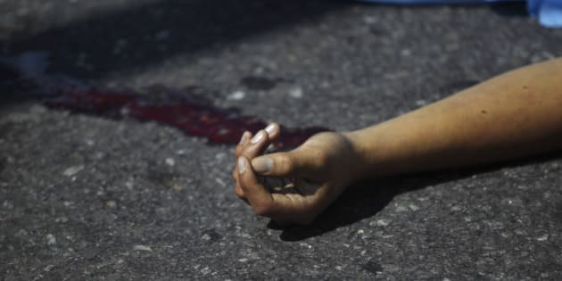 ATTENTION EDITORS - VISUAL COVERAGE OF SCENES OF INJURY OR DEATH  The hand of a man shot dead in a double homicide is seen in Zona 1 in Guatemala City, November 19, 2013. According to local media, two men were shot dead by two men riding a motorcycle. REUTERS/Jorge Dan Lopez (GUATEMALA - Tags: CRIME LAW) TEMPLATE OUT