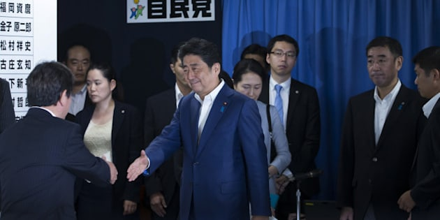 Shinzo Abe, Japan's prime minister and president of the Liberal Democratic Party (LDP), center, shakes hands with a party executive as he arrives at a conference room in the party's headquarters after the upper house election in Tokyo, Japan, on Sunday, July 10, 2016. Abe's conservative ruling coalition and its allies are set for a big win in Sunday's upper house election, an NHK exit poll showed, and may achieve the two-thirds majority that would allow him to press ahead with plans to revise the pacifist constitution. Photographer: Tomohiro Ohsumi/Bloomberg via Getty Images