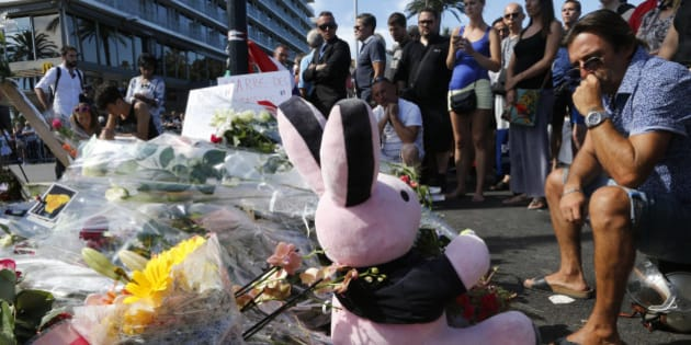 People gather near flowers, candles and a stuffed toy as they pay tribute near the scene where a truck ran into a crowd at high speed killing scores and injuring more who were celebrating the Bastille Day national holiday, in Nice, France, July 15, 2016.   REUTERS/Pascal Rossignol