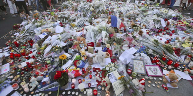 People gather at a makeshift memorial to honor the victims of an attack near the area where a truck mowed through revelers on the famed Promenade des Anglais in Nice, southern France, Sunday, July 17, 2016. French authorities detained two more people Sunday in the investigation into the Bastille Day truck attack on the Mediterranean city of Nice that killed at least 84 people, as authorities try to determine whether the slain attacker was a committed religious extremist or just a very angry man. (AP Photo/Luca Bruno)