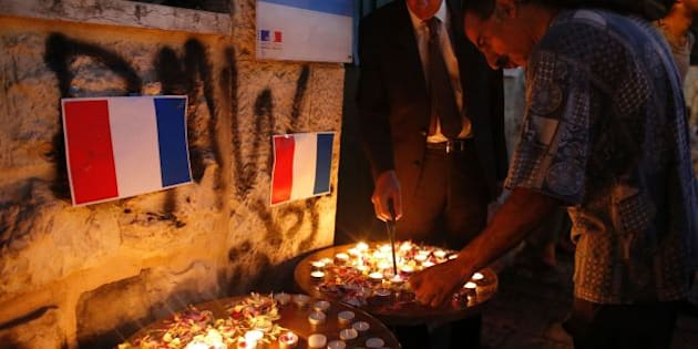 French Consul General Herve Magro (L) lights a candle during a vigil in tribute to the victims of the deadly attack  in the French Riviera city of Nice on July 18, 2016 outside the French Institute in Jerusalem. Mohamed Lahouaiej-Bouhlel, 31, rammed a 19-tonne truck into a large crowd as July 14 fireworks were ending on the Promenade des Anglais seafront in the French Riviera city, killing 84 people.   / AFP / AHMAD GHARABLI        (Photo credit should read AHMAD GHARABLI/AFP/Getty Images)