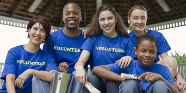 Portrait of volunteers holding painting supplies