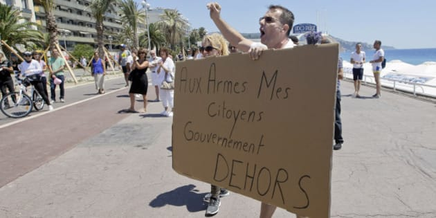 A Nice resident, Yannick, shouts slogans against government near a makeshift memorial to honor the victims of an attack on the Promenade des Anglais, in Nice, Sunday, July 17, 2016. Poster reads : Citizens take arms. Government out. French authorities detained two more people Sunday in the investigation into the Bastille Day truck attack on the Mediterranean city of Nice that killed at least 84 people, as authorities try to determine whether the slain attacker was a committed religious extremist or just a very angry man. (AP Photo/Luca Bruno)