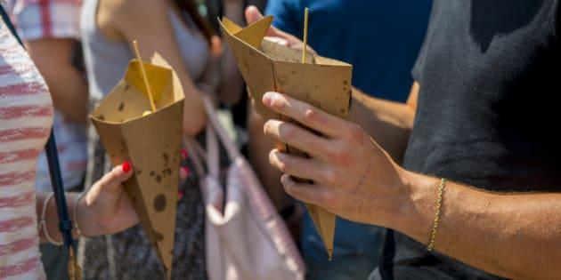 people enjoy  street food from  paper cones