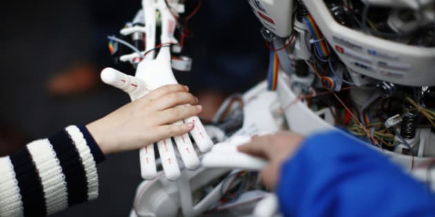 Children touch the hands of the humanoid robot Roboy at the exhibition Robots on Tour in Zurich, March 9, 2013. A project team composed of scholars and industry representatives developed the prototype of the tendon driven humanoid robot Roboy within nine months.  Roboy was unveiled to the public today during the exhibition that is marking the 25th anniversary of the Artificial Intelligence Laboratory of the University of Zurich (AI Lab). REUTERS/Michael Buholzer (SWITZERLAND - Tags: SCIENCE TECHNOLOGY SOCIETY BUSINESS)