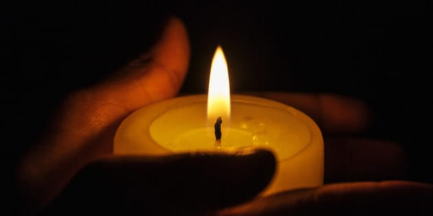 Hands holding a candle during a candle light vigil with copy space