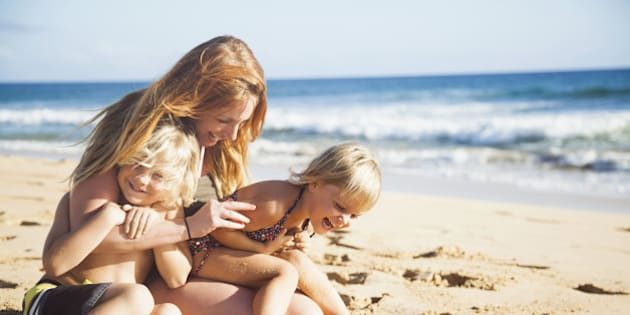 Mother with son (6-7) and daughter (2-3) on beach