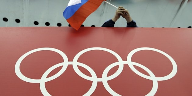 FILE - In this Feb. 18, 2014 file photo, a Russian skating fan holds the country's national flag over the Olympic rings before the start of the men's 10,000-meter speedskating race at Adler Arena Skating Center during the 2014 Winter Olympics in Sochi, Russia. The IOC's ruling 15-member executive board will meet Sunday, July 24, 2016 via teleconference to weigh the unprecedented step of excluding Russia as a whole from the 2016 Rio Olympic Games because of systematic, state-sponsored cheating. (AP Photo/David J. Phillip, file)