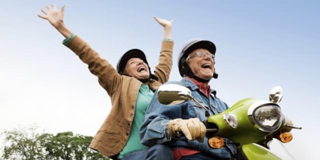 Senior couple having fun riding motor scooter. Horizontal shot.
