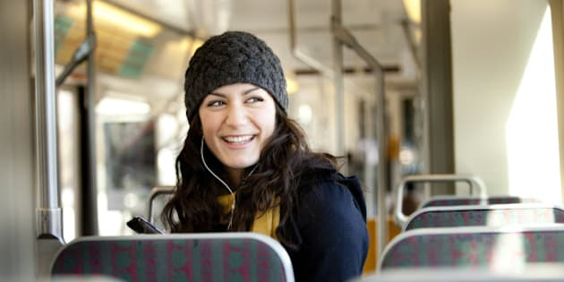 A woman listens to music while using public transportation to get around the city.