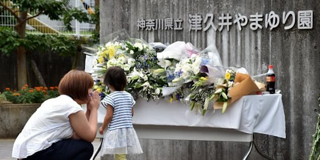 A mother and her daughter offer flowers for the victims of a knife rampage at the main entrance to the Tsukui Yamayuri En care centre in Sagamihara, Kanagawa prefecture on July 28, 2016.