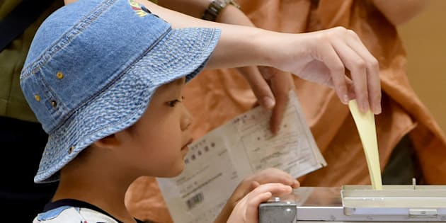 A boy watches as his mother cast her ballot at a polling station in Tokyo on July 10, 2016.  Japanese voters headed to the polls July 10 to cast their ballot in a parliamentary election with Prime Minister Shinzo Abe's ruling party expected to cruise to victory despite lukewarm support. / AFP / TORU YAMANAKA        (Photo credit should read TORU YAMANAKA/AFP/Getty Images)