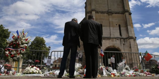 Men stand near flowers left in tribute to French priest Father Jacques Hamel outside the parish church at Saint-Etienne-du-Rouvray, near Rouen, France, July 28, 2016. Father Jacques Hamel was killed on Tuesday in an attack on the church that was carried out by assailants linked to Islamic State.  REUTERS/Pascal Rossignol