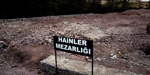 "CORRECTS PHOTOGRAPHER'S NAME - A sign reading in Turkish ""Traitors' Cemetery"" is seen in front of unmarked graves, built specifically to hold the bodies of coup plotters who died in the failed military coup of July 15, in eastern Istanbul Wednesday, July 27, 2016. In the week following the attempted coup, the local municipality announced it intended to set up a cemetery specifically for those involved - traitors who didn't deserve a decent burial. (AP Photo/Bram Janssen)"