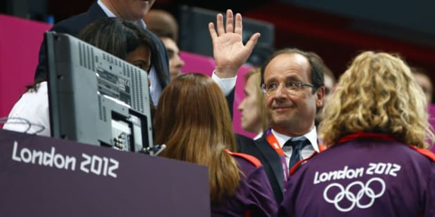France's President Francois Hollande waves as he is accompanied to his seat by British Prime Minister David Cameron (L) during the women's handball Preliminaries Group B match between France and Spain at the Copper Box venue during the London 2012 Olympic Games July 30, 2012. REUTERS/Marko Djurica (BRITAIN  - Tags: POLITICS SPORT HANDBALL SPORT OLYMPICS)