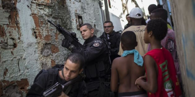 """Special Operations Battalion (BOPE) Police officers patrol as residents move about the Sao Carlos slum complex where the bodies of two men were found in Rio de Janeiro, Brazil, Friday, May 15, 2015. The bodies of two young men were discovered late Thursday in this so-called """"pacified"""" slum where police are present. (AP Photo/Felipe Dana)"""