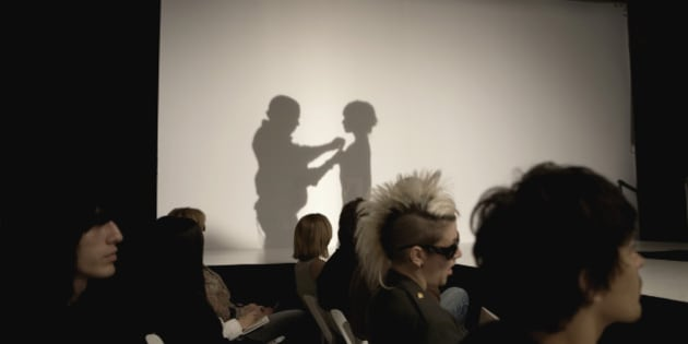 Fashion show with shadow of people from backstage on screen