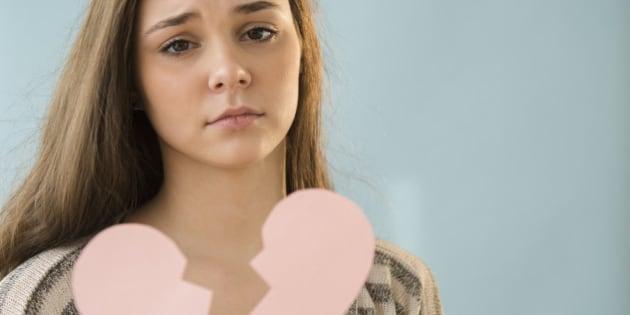 Hispanic girl holding broken heart shape