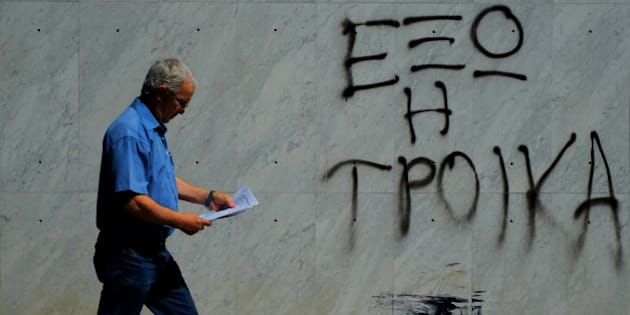 "A man holds papers as he passes outside of a branch of Bank of Cyprus with a painting that reading in Greek ""Troika out"" in downtown capital Nicosia, Cyprus,  Wednesday, June 18, 2014. Cyprus made its return to the international markets Wednesday in its first public bond issue  since last year's painful rescue deal that saved it from bankruptcy. (AP Photo/Petros Karadjias)"
