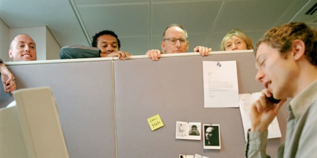 Office workers listening to male colleague on telephone