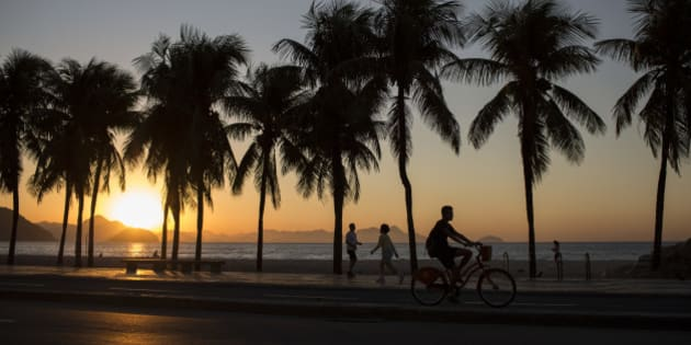 People exercise along Copacabana beach as the sun rises in Rio de Janeiro, Brazil, Wednesday, July 27, 2016. The iconic beach will be the starting point for the road cycling race, marathon swimming and triathlon competitions during the Olympics. (AP Photo/Felipe Dana)