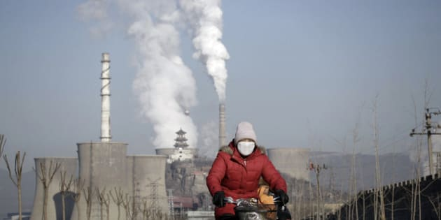 A woman wearing a mask rides past smoking chimneys and cooling towers of a steel plant in Beijing, January 17, 2013. Chinese leaders dazzled the world by clearing the skies as if by edict before the Beijing Summer Olympics in 2008. Fast forward to January 2013, and the government seems powerless against those same skies, tarnished by an opaque, toxic cloud that has smothered the city for nearly a week. REUTERS/Suzie Wong (CHINA - Tags: BUSINESS ENVIRONMENT)