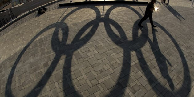 A man walks past a shadow of a set of Olympic rings in the Olympic Park ahead of the Rio 2016 Summer Olympics, in Rio de Janeiro, Brazil, Thursday, Aug. 4, 2016. (AP Photo/Charlie Riedel)