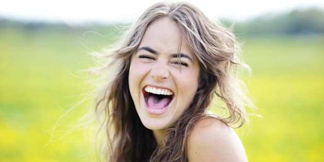Woman laughing with her eyes closed .
