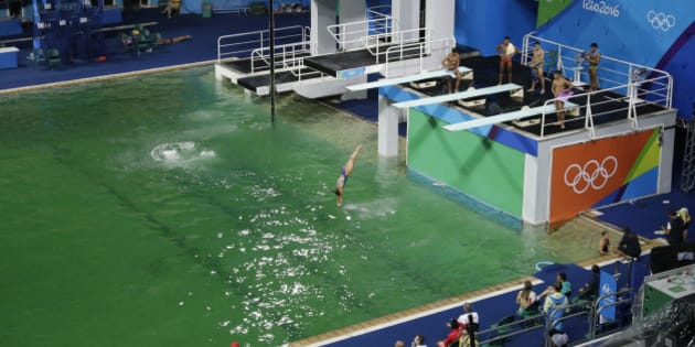 The water of the diving pool appears a murky green, in stark contrast to the pool's previous day's color and also that of the clear blue water in the second pool for water polo at the venue as divers train in the Maria Lenk Aquatic Center at the 2016 Summer Olympics in Rio de Janeiro, Brazil, Tuesday, Aug. 9, 2016. (AP Photo/Matt Dunham)