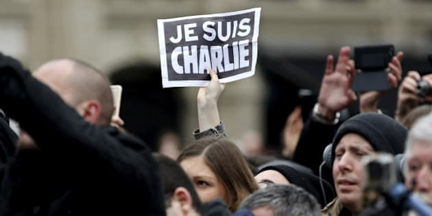 "A person holds up a ""Je Suis Charlie"" (I am Charlie) sign during a ceremony at Place de la Republique square to pay tribute to the victims of last year's shooting at the French satirical newspaper Charlie Hebdo, in Paris, France, January 10, 2016. France this week commemorates the victims of last year's Islamist militant attacks on satirical weekly Charlie Hebdo and a Jewish supermarket with eulogies, memorial plaques and another cartoon lampooning religion.  REUTERS/Yoan Valat/Pool"
