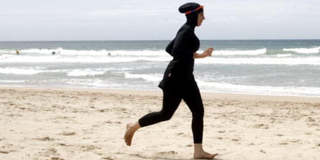 "Twenty-year-old trainee volunteer surf life saver Mecca Laalaa runs along North Cronulla Beach in Sydney during her Bronze medallion competency test January 13, 2007. Specifically designed for Muslim women, Laalaa's body-covering swimming costume has been named the ""burkini"" by its Sydney based designer Aheda Zanetti.   REUTERS/Tim Wimborne (AUSTRALIA)"