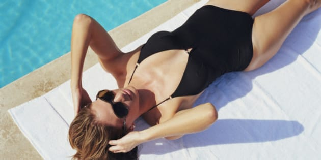 Woman lying by side of pool, elevated view