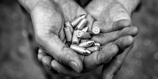 Semiautomatic pistol ammunition in mans hands.