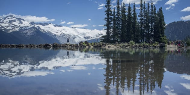 Reflections of trees and snow covered mountain on Garibaldi Lake
