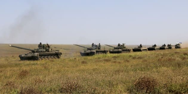 A column of Ukrainian tanks and APCs move towards the de-facto border with Crimea near Kherson, southern Ukraine, Friday, Aug. 12, 2016. Ukraine put its troops on combat alert Thursday along the country's de-facto borders with Crimea and separatist rebels in the east amid an escalating war of words with Russia over Crimea. (AP Photo/Aleksandr Shulman)