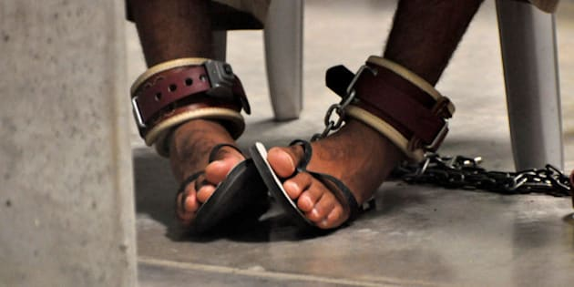 """FILE PHOTO -  In this photo, reviewed by a U.S. Department of Defense official, a Guantanamo detainee's feet are shackled to the floor as he attends a """"Life Skills"""" class inside the Camp 6 high-security detention facility at Guantanamo Bay U.S. Naval Base April 27, 2010. REUTERS/Michelle Shephard/Pool/File Photo"""