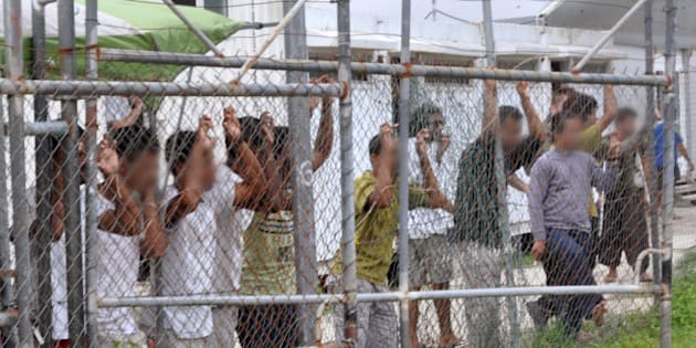 Asylum-seekers look through a fence at the Manus Island detention centre in Papua New Guinea March 21, 2014. Eoin Blackwell/AAP/via Reuters/File Photo ATTENTION EDITORS - FACES PIXELLATED AT SOURCE. THIS PICTURE WAS PROVIDED BY A THIRD PARTY. EDITORIAL USE ONLY. NO RESALES. NO ARCHIVE. AUSTRALIA OUT. NEW ZEALAND OUT.?