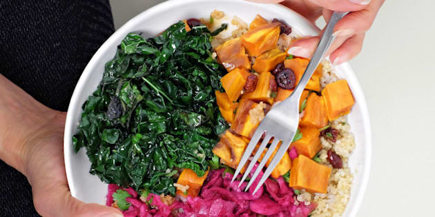 Close cropped overhead view of woman sitting cross legged on floor with bowl of healthy vegan food. Quinoa, kale, sweet potato, sauerkraut - sometimes called Buddha Bowl or Hippie Bowl