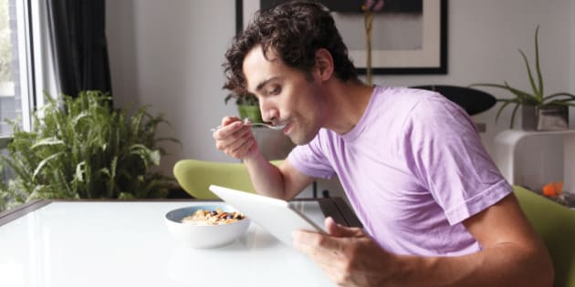 Man reading digital tablet and eating cereal